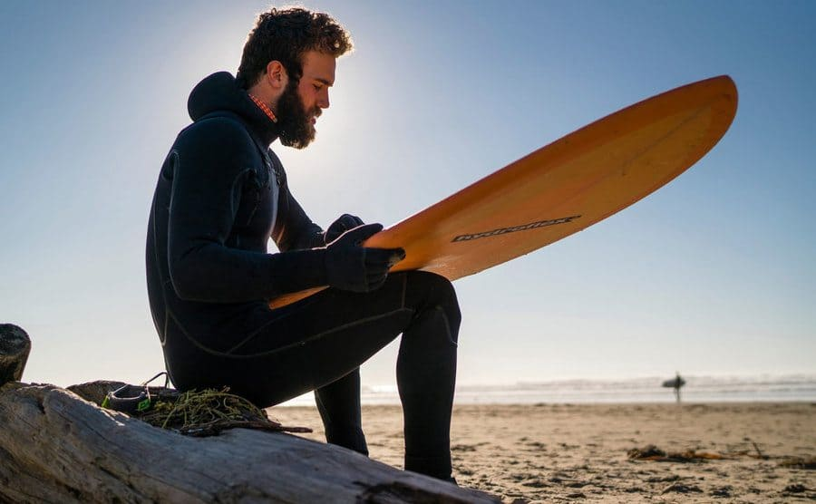 Daniel waxing his surfboard on the beach.