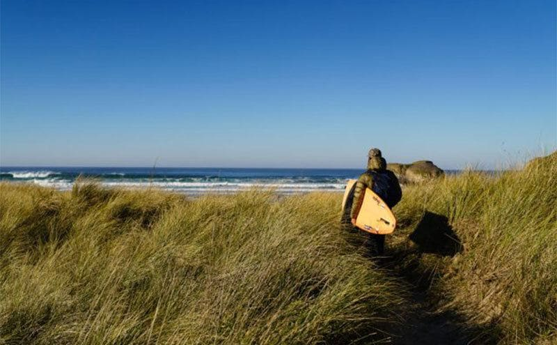 David carrying his paddleboard towards the beach.