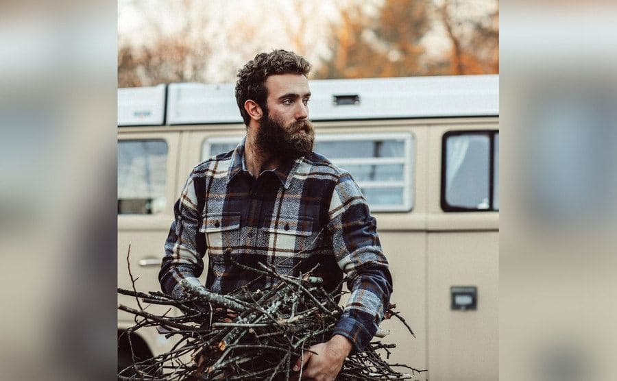 Daniel sporting his full beard while carrying wood for a fire.