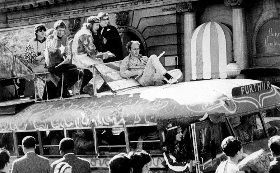 Ken Kesey, on top of the Furthur Bus, is holding a flute in San Francisco.