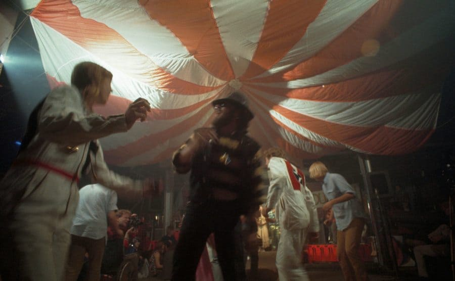 Doris Delay, dressed in a white jumpsuit, dances with a member of the Hell's Angels at the Acid Test Graduation.