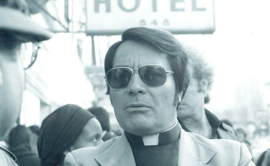 Jim Jones in preacher attire sitting in a café.