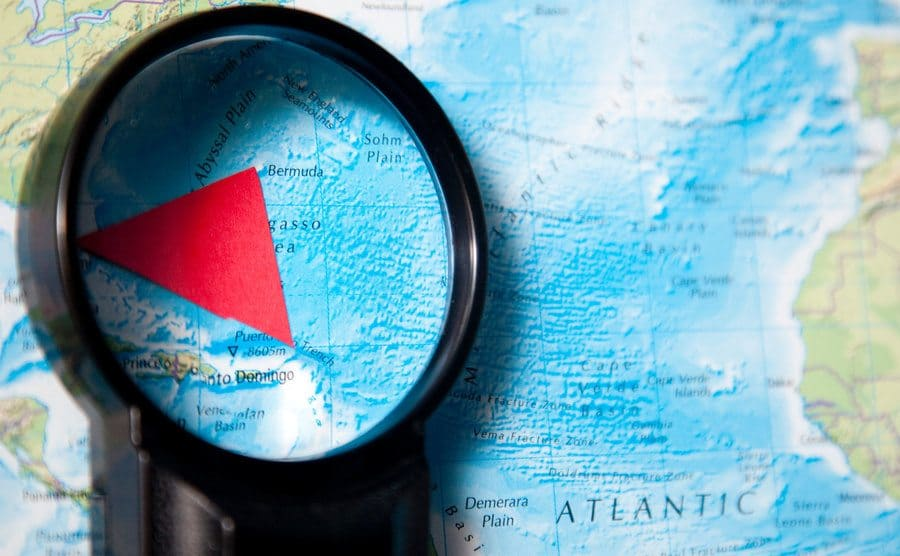 magnifying glass investigates the Bermuda triangle on a map.