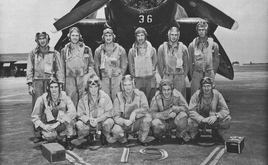 A military flight crew posing for a picture in front of their plane, with the number 19 on the floor before them.