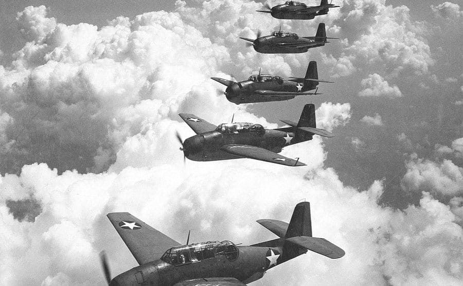 Five military planes are flying in formation.