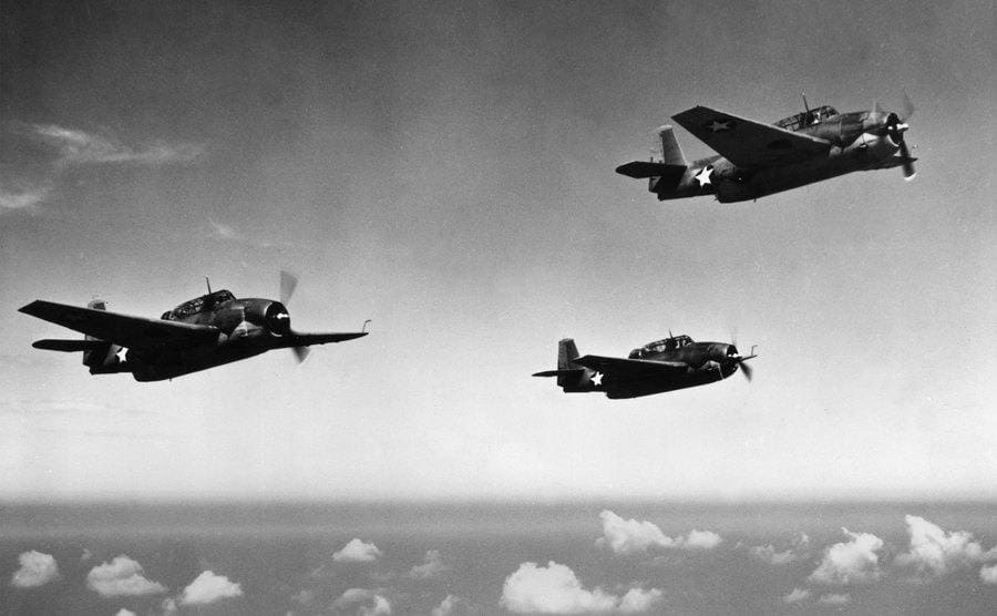 Three all-purpose bombers are flying above the ocean.