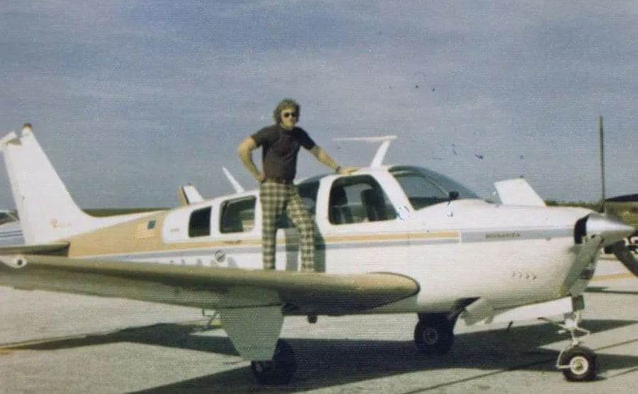 Bruce Gurnon is standing on the wing of his small plane.