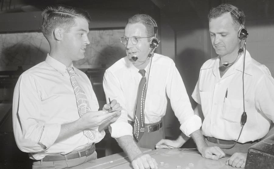 Radar experts are talking in a radar room while examining a map.