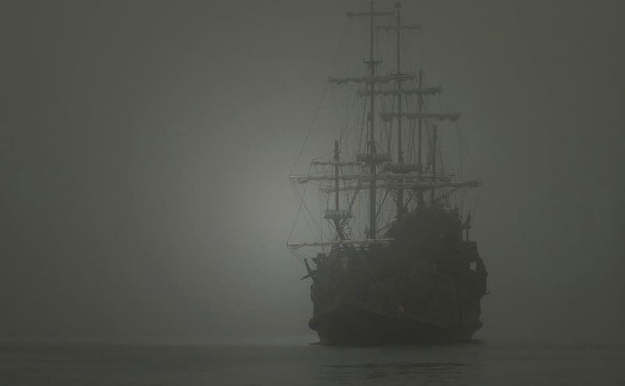 A lone ship out on the water surrounded by fog.