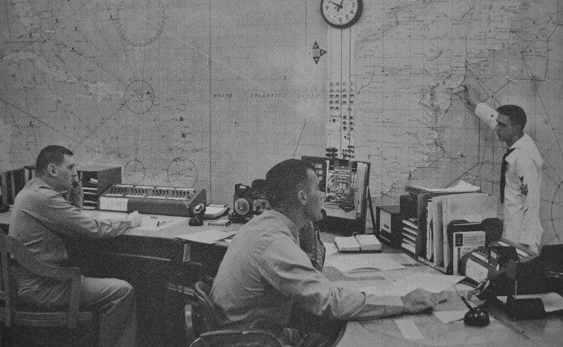 The coast guard looking into a rescue plan in the control room.