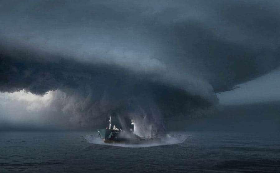 A large ship being pulled into a vortex in the ocean.