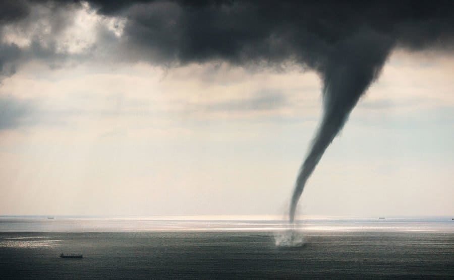 A large cargo ship near a tornado formed in the ocean.