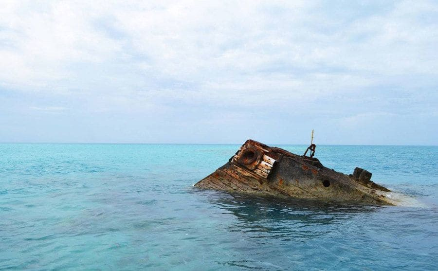 An old and rusty shipwreck slightly exposed above the water.