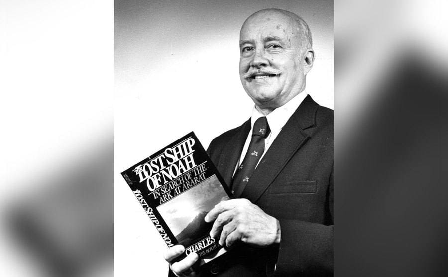 A press photo of Charles Berltiz holding one of his books.