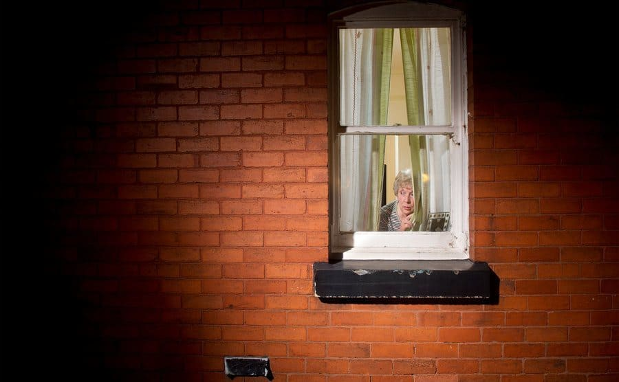 A grandma looking out her window suspiciously