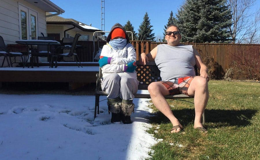 A woman sitting in the shade in full winter clothing with snow on the ground while he husband sits beside her in the sun in summer clothing, and the snow has melted away.