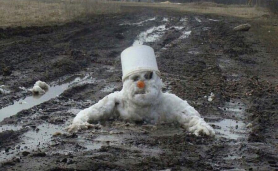 A snowman appears to be melting into the gross dirty snow left on the ground.