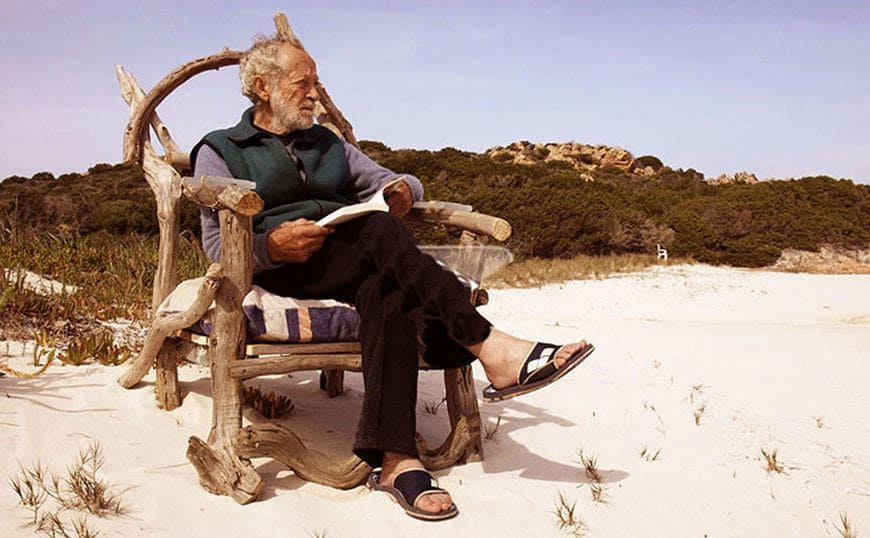 Mauro Morandi is sitting in a makeshift chair he made reading a book.