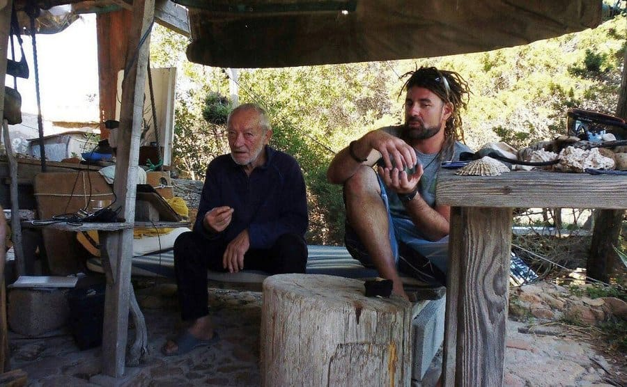 Mauro Morandi is sitting beside a young man in the shack he built for himself.