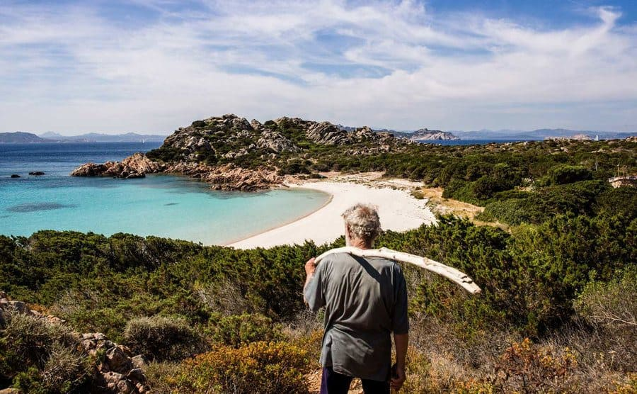 Morandi is overlooking the cove from the hilltop while holding a large stick on his shoulder.
