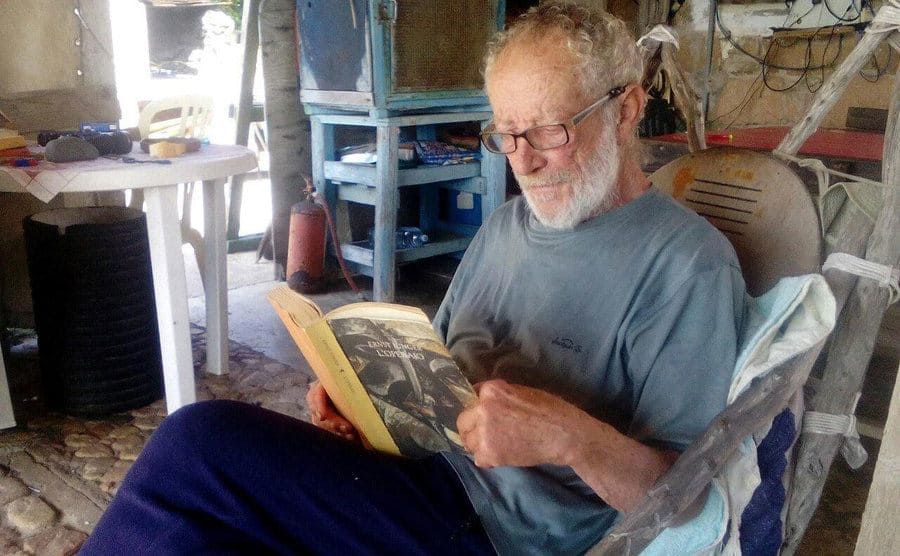 Morandi is sitting in his home on the island reading a book.