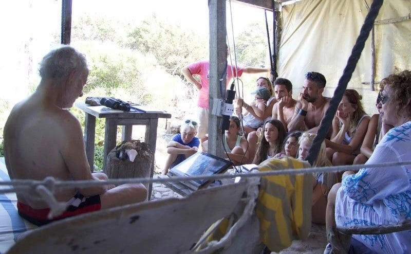 Morandi is sitting in his shack in front of a group of tourists telling them about the island.