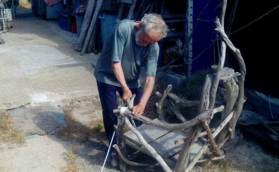 Morandi is building an oversized chair out of thick branches he found around the island.