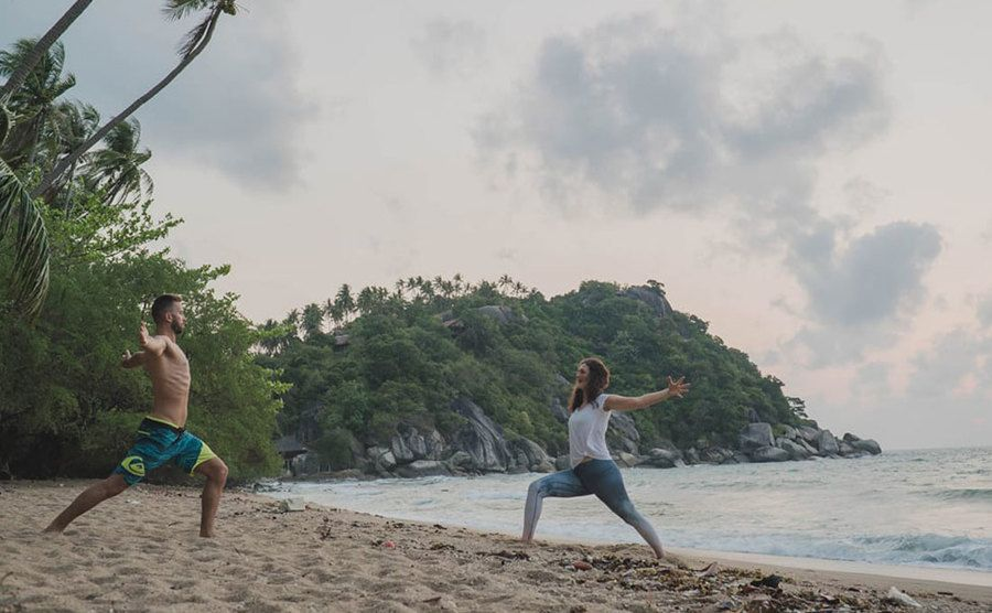 Guests are practicing yoga by the beach.