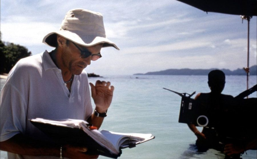 Danny Boyle reads the script by the beach.