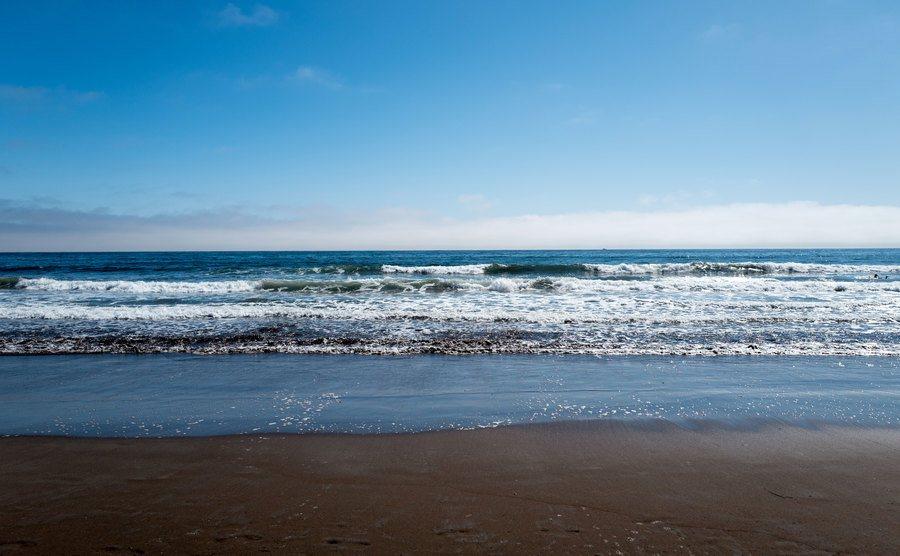 Waves break on the shore.