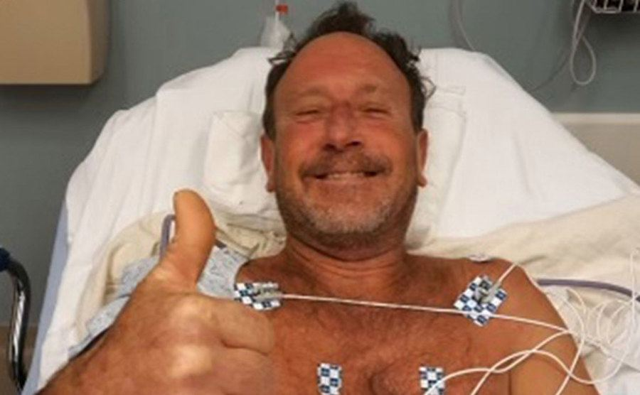 Michael smiles at the camera while lying on the hospital bed.