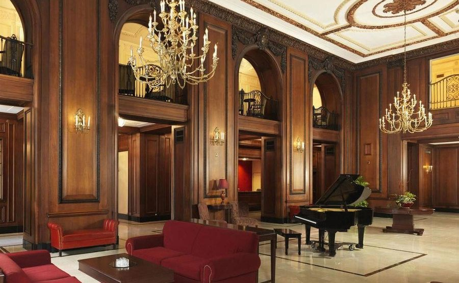 Red sofas, a piano, and chandeliers decorate the hotel's interior.