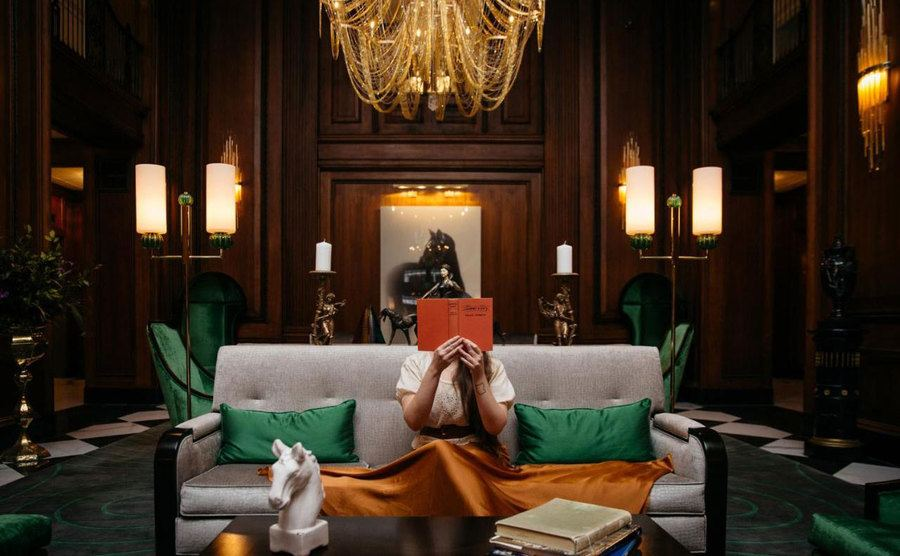 A woman reading a book on one of the hotel's sofas.
