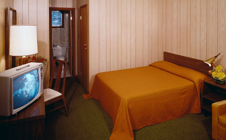 A wooden bed with orange sheets facing an old TV set.