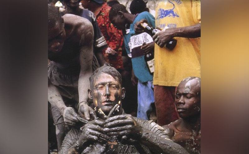 Benedict Allen takes part in a local ritual while he sits covered in mud surrounded by locals.