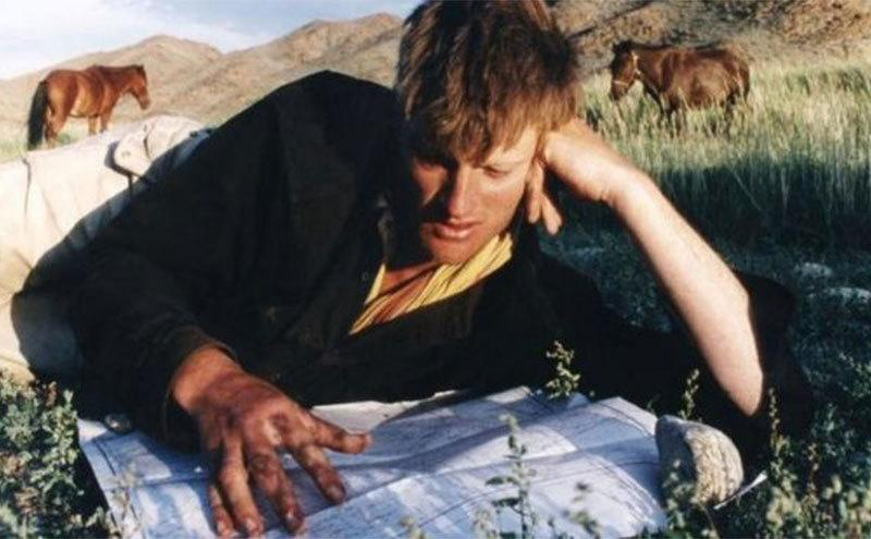 Benedict Allen looks over a map while resting in the grass.