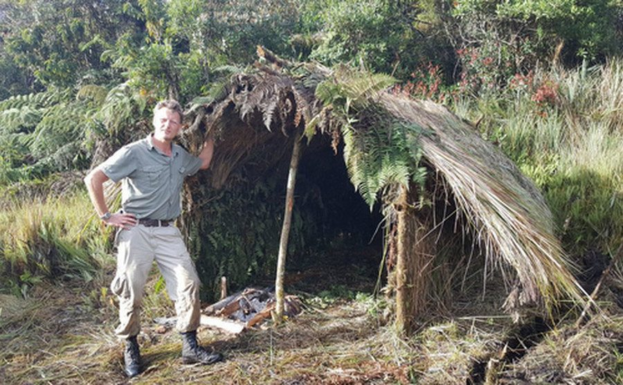 Benedict Allen stands beside a shelter made out in the middle of the jungle.