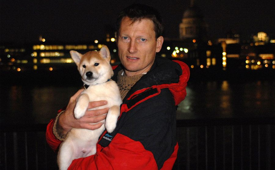 Benedict Allen stands on a bridge while holding a dog in his arms.