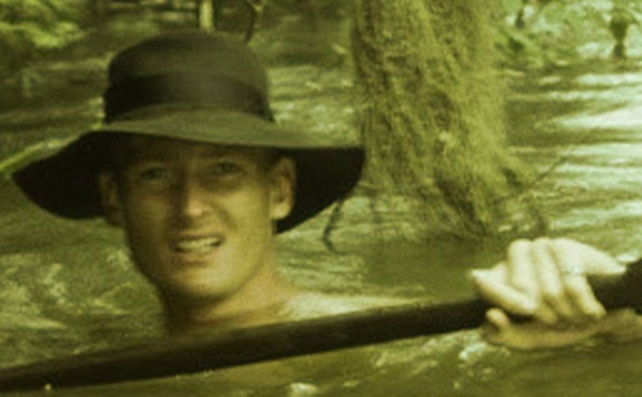 Allen walks through the river with a canoe paddle in his hands.