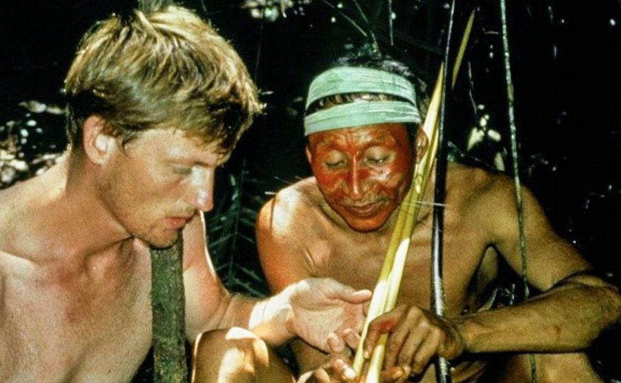 Benedict Allen is being shown customs by a local in the Amazon jungle.