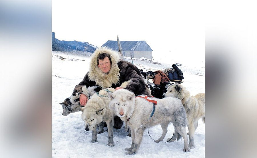 Benedict Allen poses with him slay dogs while on a trip in Siberia.
