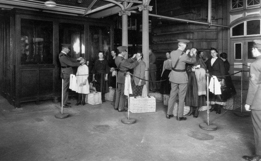 Immigrants wait in line upon arriving at Ellis Island.