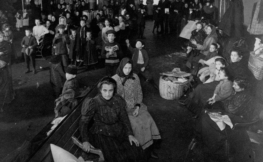 Immigrants sit and stand in the waiting room of Ellis Island.