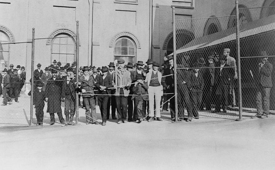 Immigrants stand behind a fence at Ellis Island.