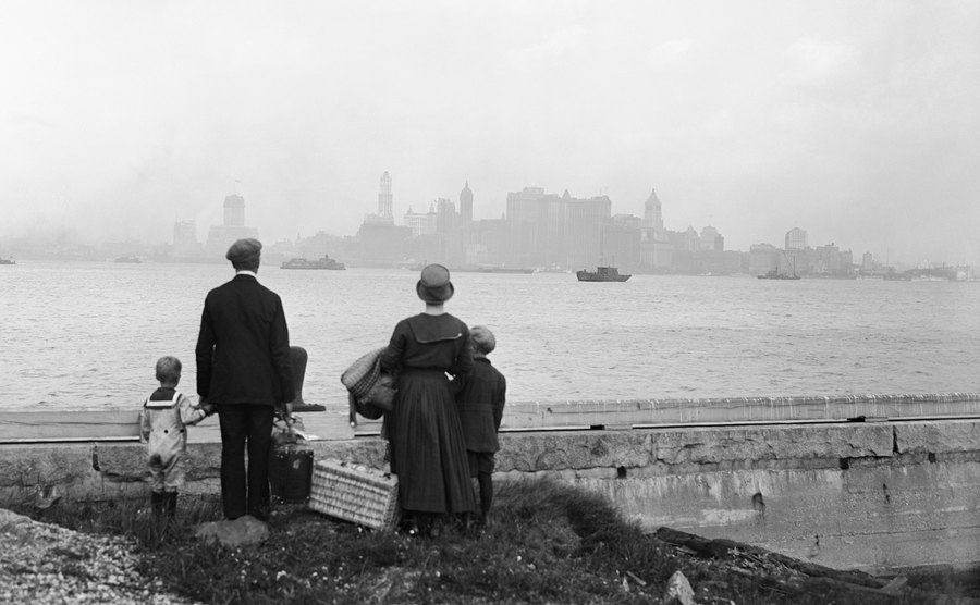 A little immigrant family on the dock at Ellis Island.