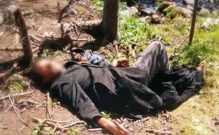 A photo of a man lying down in the forest.