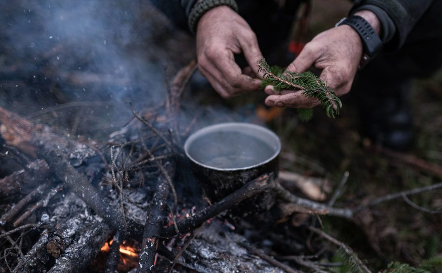 A photo of a man making tea in a forest.