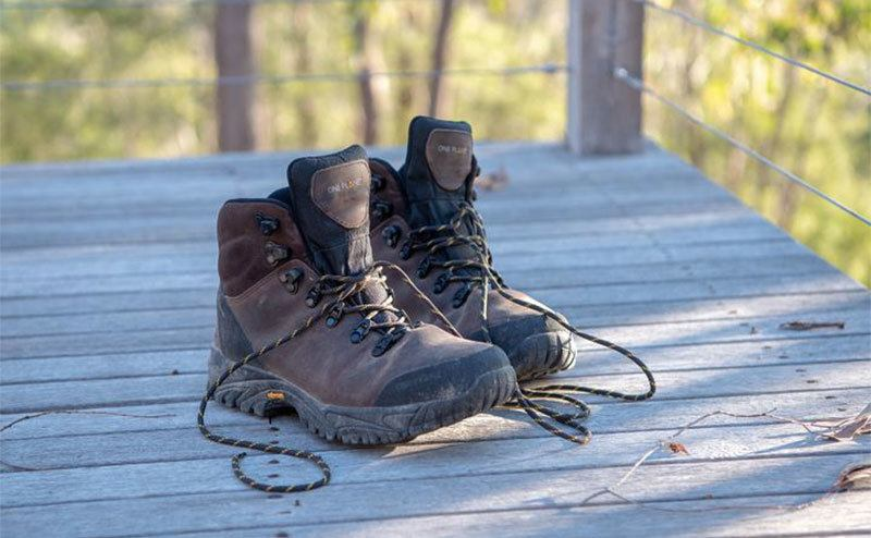 A photo of hiking shoes on a wooden deck.