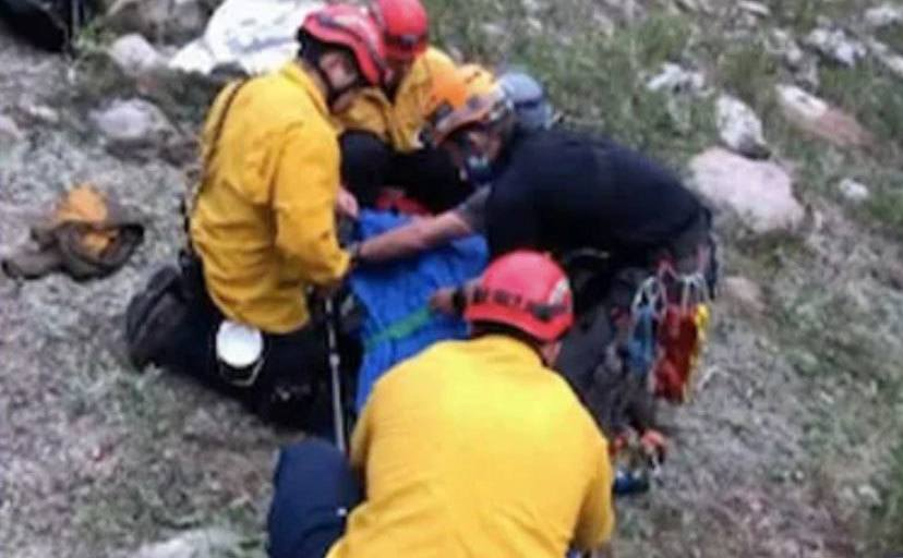 The rescue team is assisting the hiker.
