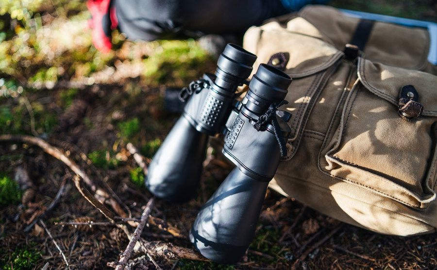 A close-up of a backpack and binoculars on the ground in nature.